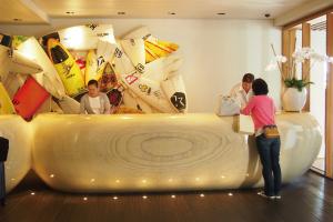 【フロントデスク】壁に展示されたサイン入りのサーフボードのオブジェがみなさまをお迎えいたします。