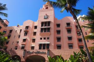 【華やかで空の色とのコントラストが美しい外観(本館)】青い海、青い空、緑溢れるガーデンに映えるコーラルピンク色が美しいザ・ロイヤルハワイアンホテル。